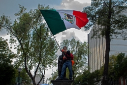 HOMBRE MUEVE BANDERA DE MEXICO EN CALLE ALVARO OBREGON COLONIA ROMA